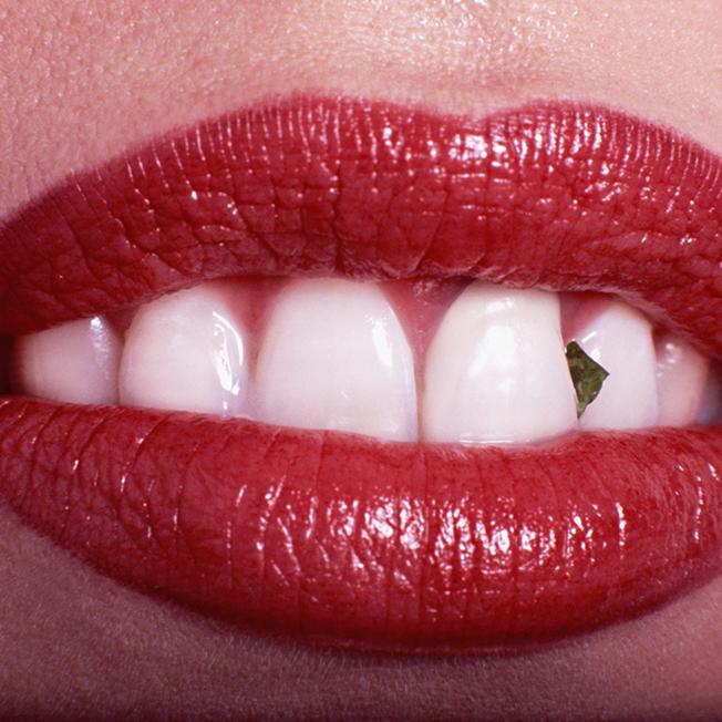 bouche de femme avec morceau de salade