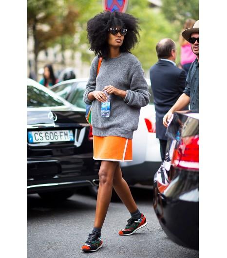 Profitez de la tendance sportive et stylisez votre sweat avec une mini jupe lumineuse et des sneakers colorées. Image viaGastro Chic